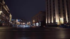 Zwarte auto met opvlammende lichten die kruising overgaan Andere tegengehouden auto's nacht stock footage