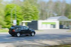 Zwarte auto in motie op asfaltweg en groene bomen stock foto
