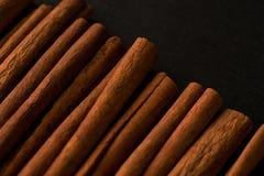Zwarte backgroud van de pijpjes kaneel donkere foto Stock Afbeeldingen