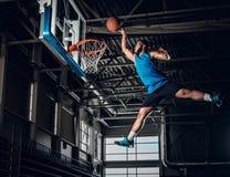 Zwarte basketbalspeler in actie in een basketbalhof stock foto