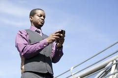 Zwarte bedrijfsmens die met slimme telefoon werkt stock foto's
