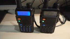 Zwarte behandelde draagbare walkie-talkie radiozender die en in dark werken opvlammen stock videobeelden