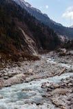Zwarte berg met sneeuw op de bovenkant Ter plaatse is bevroren rivier met witte steen en ijs bij de vallei van Thangu en Chopta-i Stock Foto's