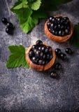 Zwarte bes met bladeren in houten kommen Stock Foto
