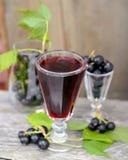 Zwarte besalcoholische drank en rijpe bessen op houten stock fotografie