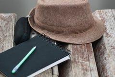 Zwarte blocnote, groene pan, glazengeval en hoed op bank in park dichte omhooggaand royalty-vrije stock afbeelding