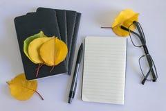 Zwarte blocnote voor nota's en gele bladeren op een witte achtergrond Stock Foto's