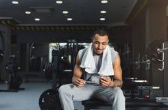 Zwarte bodybuilder die mobiele telefoon met behulp van bij gymnastiek stock foto's