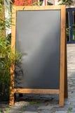Zwarte bordtribune op hout voor een restaurantmenu in stre royalty-vrije stock foto