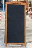 Zwarte bordtribune op hout voor een restaurantmenu in stre stock afbeelding
