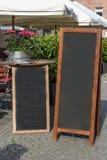 Zwarte bordtribune op hout voor een restaurantmenu in stre stock foto's