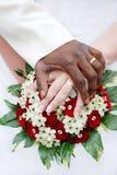 Zwarte bruidegom en witte fiancehanden op boeket Royalty-vrije Stock Foto