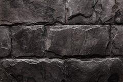 Zwarte bruine de textuur van de Steenmuur natuurlijke kleur als achtergrond Royalty-vrije Stock Foto's
