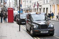 Zwarte cabines die in de Nieuwe straat van de Band in Londen worden geparkeerd. Royalty-vrije Stock Foto's