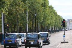 Zwarte Cabines op hun manier aan Buckingham Palace in Londen stock foto's