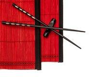 Zwarte Chinese eetstokjes op rode bamboemat Aziatische Stijl royalty-vrije stock afbeelding