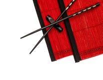Zwarte Chinese eetstokjes op rode bamboemat Aziatische Stijl stock fotografie