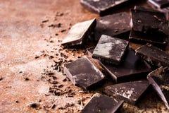 Zwarte chocoladestukken op bruine achtergrond Stock Afbeelding