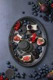 Zwarte crackers met kaas en bessen Stock Foto's