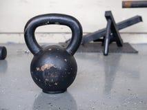 Zwarte, de zitting van 10 kg kettlebell op harde gymnastiekvloer Royalty-vrije Stock Afbeeldingen