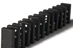 Zwarte die domino's op een witte achtergrond worden ge?soleerd De ruimte van het exemplaar royalty-vrije stock afbeelding