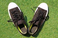 Zwarte die tennisschoenen op groen gras worden geplaatst royalty-vrije stock fotografie