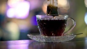 Zwarte die thee in een zak in een glaskop wordt gebrouwen stock video