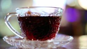 Zwarte die thee in een zak in een glaskop wordt gebrouwen stock footage