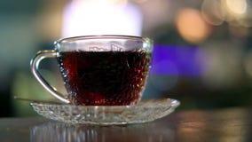 Zwarte die thee met warm water in een glaskop wordt gebrouwen stock videobeelden