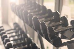 Zwarte domoorreeks Sluit omhoog vele metaaldomoren op rek in sportfitness centrum, het concept van het Gewichtheffenmateriaal royalty-vrije stock afbeelding