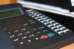 Zwarte draadtelefoon met knopen en vertoning op bureau in bureau stock fotografie