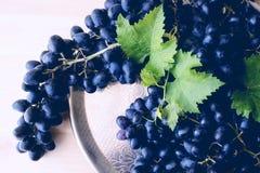 Zwarte druiven op een zilveren dienblad De zomer royalty-vrije stock foto's