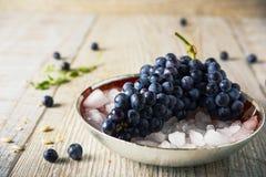 Zwarte druiven op het verpletterde ijs, selectieve nadruk Stock Afbeelding
