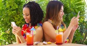 Zwarte en Aziatische beste vrienden op vakantie die mobiele telefoons met behulp van stock afbeeldingen