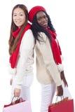 Zwarte en Aziatische vrouw met het winkelen zakken op Kerstmis Stock Afbeeldingen