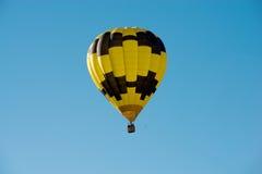 Zwarte en gele hete luchtballon in een blauwe hemel Stock Fotografie
