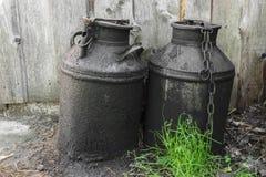 Zwarte en geoli?de metaalbussen in het platteland Houten muur stock foto