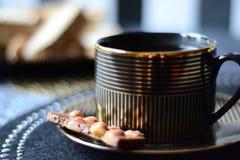 Zwarte en gouden koffiekop met chocoladereep royalty-vrije stock foto's