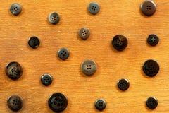 Zwarte en grijze naaiende knopen op hout Stock Foto's