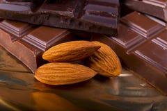 Zwarte en melkchocola met noten op een folie Stock Fotografie