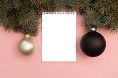 Zwarte en parel de Kerstmisballen op de roze achtergrond met pijnboomboom vertakt zich stock afbeelding