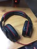 Zwarte en Rode Hoofdtelefoons op Houten Bureau Stock Afbeelding