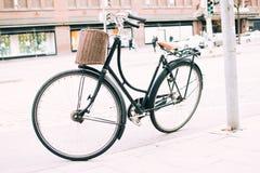Zwarte fiets die op de stoep wordt geparkeerd stock afbeelding