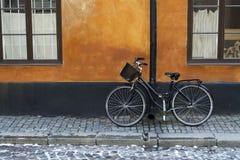 Zwarte fiets met mand op rode muur, Stockholm, Zweden Stock Fotografie