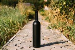 Zwarte fles op de weg van de tegels, het dorp, landelijk alcoholisme, dronkenschap alcoholische ziekte wijn natuurlijke drank Wij stock afbeelding