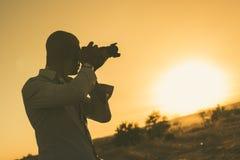 Zwarte fotograaf bij zonsondergang stock foto's