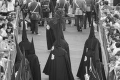 Zwarte geklede Nazarenes die een kruis dragen tijdens een Pasen-optocht Royalty-vrije Stock Fotografie