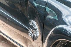 Zwarte gekraste auto met beschadigde verf in neerstortingsongeval op de straat of botsing op parkeerterrein in de stad met gedeuk royalty-vrije stock fotografie