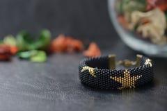 Zwarte geparelde armband met gouden sterren Stock Afbeeldingen