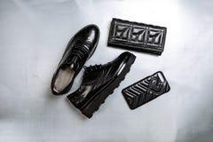 Zwarte geperforeerde schoenenoxfords, een beurs en een telefoongeval op een document witte achtergrond stock afbeelding